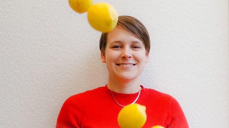tolino media Mitarbeiterin Laura mit rotem Pullover und Zitronen, die in die Luft geworfen wurden