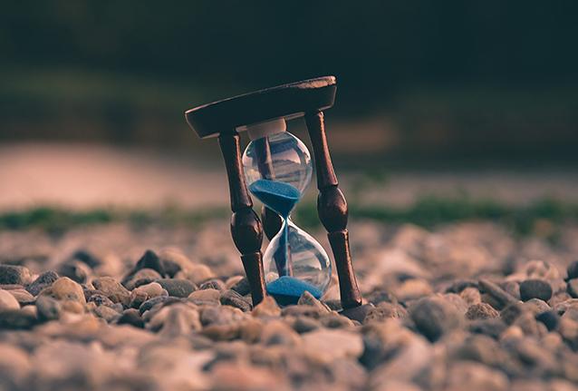 Sanduhr mit blauem Sand auf Kiesstrand, Symbol Zeitreiseromane