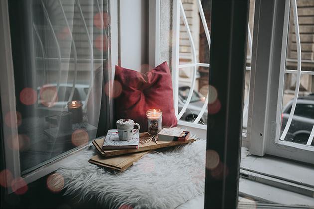 Idyllische Szene. Ein offenes Fenster. Ein rotes Kissen liegt darangelehnt. Darunter liegt eine flauschige weiße Decke. Auf der Decke steht ein kleines Tablett mit einer Tasse Kaffe und einer Kerze darauf